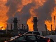 image of orange sky with smoke stacks and smoke