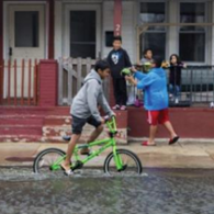 Kid on bike on flooded street
